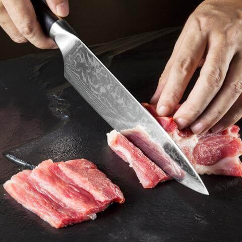 Image du couteau en train d'être utilisé pour couper de la viande.