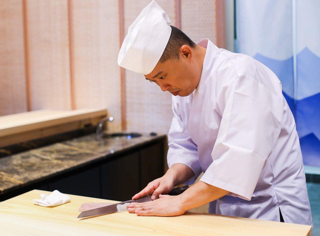 Chef japonais travaillant le poisson pour en faire des sashimis, un plat demandant beaucoup de rigueur